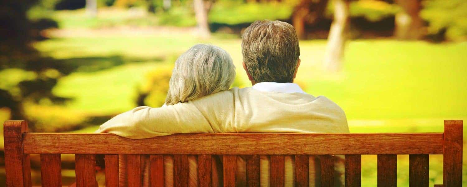 An older couple sitting on a park bench.
